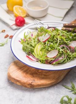 新鮮な緑のルッコラは白いボウル、リンゴ、大根、ピーカンナッツ、タマネギのテキストと木製の素朴な背景にタマネギのルッコラロケットサラダに葉します。トップビュー、健康食品、ダイエット。栄養の概念