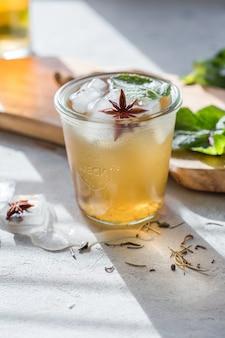 昆布茶またはアイスティー飲料。発酵スーパーフード、ガラスのプロバイオティックサマードリンク、ガラス、ミント、レモン、コンクリートテーブル