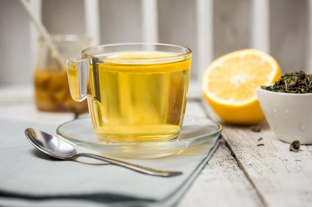 Чай в стеклянной чашке с листьями мяты сушеный чай нарезанный лимоном.