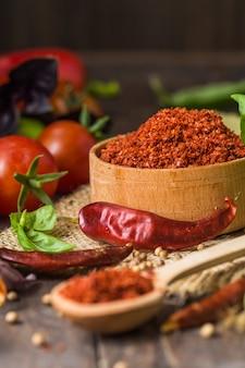 Специи паприки или холодного перца на деревянной стене. грузинские специи, индийские специи, арабские специи. разнообразие специй. травы и специи