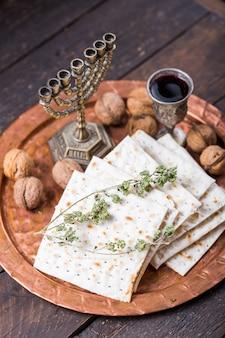 Пасха, праздник опресноков, хлеб мацы и бокалы для красного вина на круглом металлическом подносе.