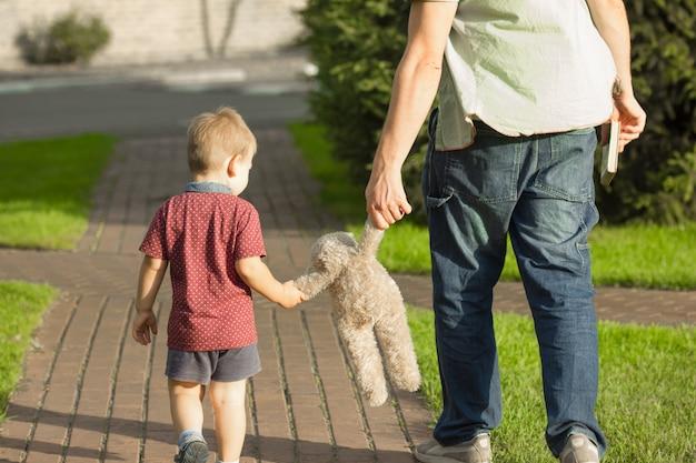 Маленький мальчик держит руку своего отца и медведя