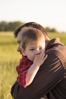 Улыбающийся молодой папа и сын обнять расслабляющий на лугу.