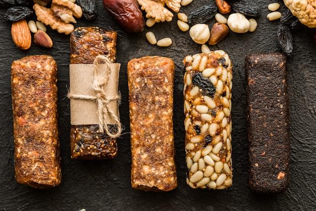 Медовые батончики с арахисом, кунжутом и семечками карамели. закуски из семян, орехов и кунжута с медом на фоне деревянные. засахаренные орехи.