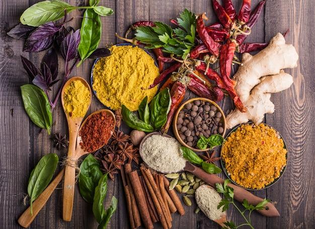 Специи. различные индийские специи на черном каменном столе. специи и травы на фоне шифера. ассортимент приправ, приправ. готовим ингредиенты, ароматизаторы