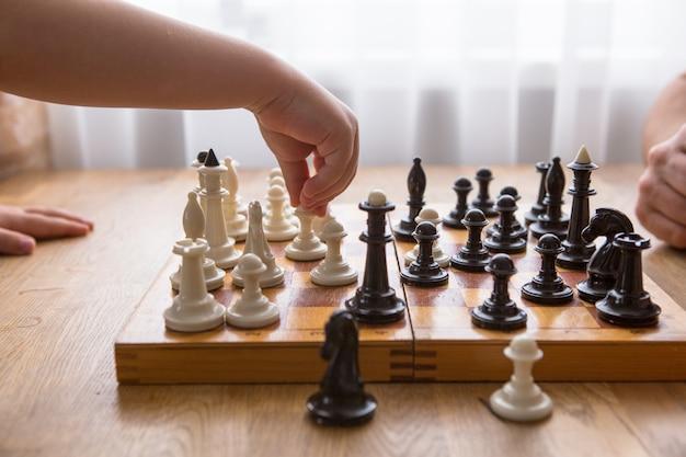 Папа и сын играют в шахматы вместе дома