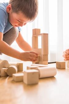 Молодой папа играет со строительным кирпичом с маленьким сыном
