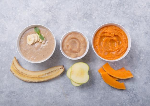 カラーテーブルに健康なベビーフードのボウル。ピューレ、新鮮な有機果物や野菜、フレイレイ、上面図、コンセプトで作られました。キッズミール