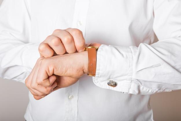 彼の手の空き領域で時計を見て実業家のクローズアップ。