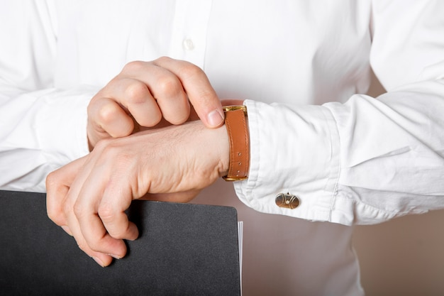 彼の手の空き領域で時計を見て実業家のクローズアップ。高級腕時計からの時間をチェックする白いシャツの男。新郎の結婚式の準備。