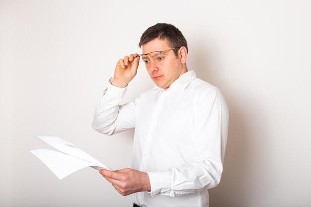 Портрет смешного кавказского бизнесмена сотрясенный удивленный с открытыми стеклами для того чтобы увидеть финансовый отчет, концепцию плохой новости