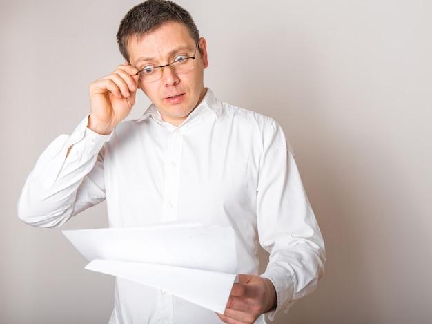 Портрет смешного кавказского бизнесмена сотрясенный удивленный с открытым ртом для того чтобы увидеть финансовый отчет, концепцию плохой новости