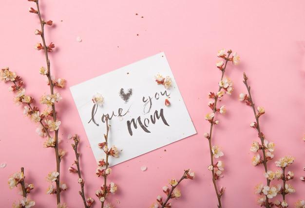 Люблю тебя, мама рукописная надпись. ручной обращается надписи, каллиграфия. открытка с весенним деревом бранч фон, день матери.