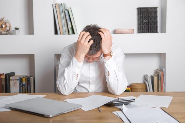 悲しいマネージャーは解雇の通知を受け取り、ラップトップと財務書類を持って職場に座って、従業員は悪い知らせの手紙を受け取った、起業家は商業的失敗または会社の破産に動揺