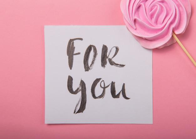 Для вас рукописная надпись. ручной обращается надписи, каллиграфия. открытка с розовой розой конфеты в пастельных тонах на деревянной палочке на сером фоне, валентина, день матери.
