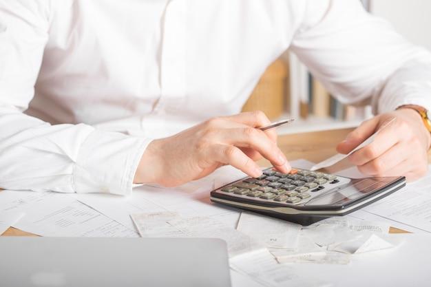 Закройте вверх ручки удерживания руки бизнесмена или бухгалтера работая на документе бухгалтерии калькулятора и портативном компьютере на офисе, концепции дела
