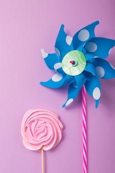 Розовая, желтая розовая конфета с красочными игрушечными ветряными мельницами в пастельных тонах на деревянной палочке на сером фоне