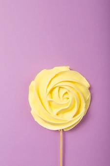 Желтая роза в пастельных тонах на деревянной палочке на сером фоне