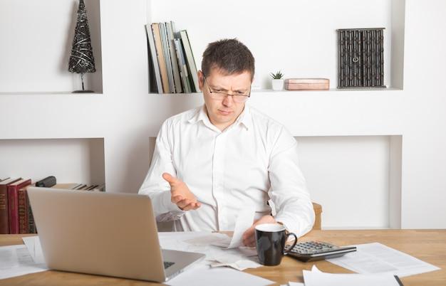 Зрелый владелец малого бизнеса, рассчитывающий финансовые счета деятельности - он - удивленное лицо, взволнованное выражением страха