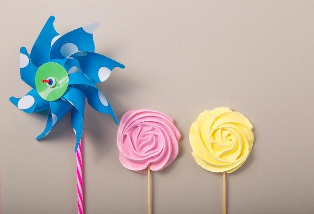 灰色の背景、バレンタイン、母の日に木の棒にパステルカラーのカラフルなおもちゃの風車とピンク、黄色のバラのお菓子。