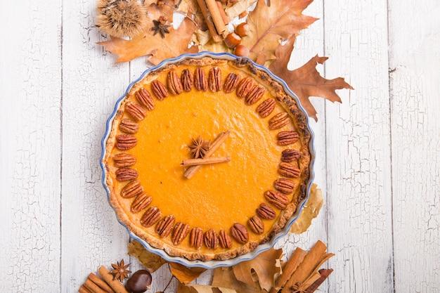 ピーカンナッツと素朴な背景にシナモンとカボチャのパイ。感謝祭のための手作りの秋のペストリー
