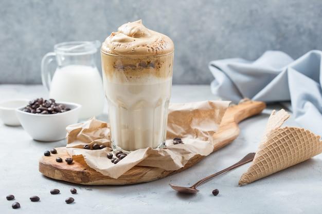 食品トレンド-ダルゴナコーヒー、素朴な背景にインスタントドリンクをホイップ