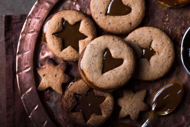 木製の背景上の自家製クリスマス新年星形キャラメルクッキー。フラットレイアウト、スペース。