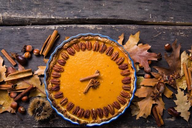 ピーカンナッツとシナモンの素朴な背景、平面図、コピースペースのカボチャのパイ。感謝祭のための手作りの秋のペストリー
