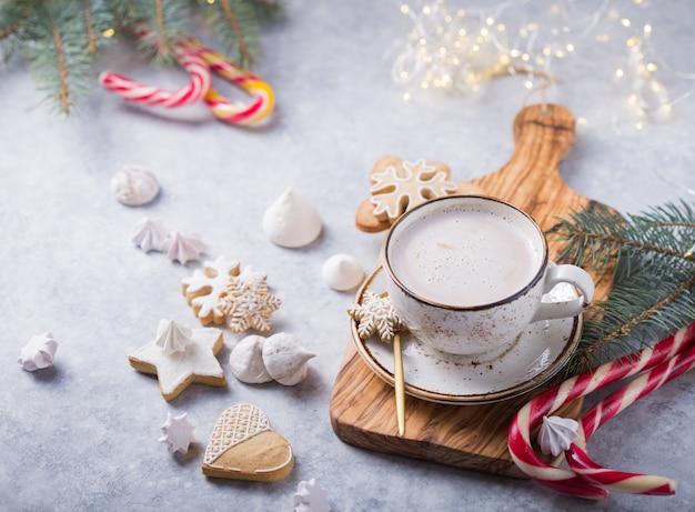 ホットチョコレートカカオは、灰色の表面に白いクリスマスマグカップにジンジャーブレッドを飲みます。伝統的な休日のホットドリンク、クリスマスや新年のお祝いカクテル。上面図