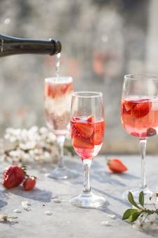 Красное вино сангрия или пунш с фруктами и льдом в очках и пинчере. домашняя освежающая фруктовая сангрия.