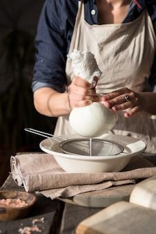 ココナッツミルクの準備-チーズクロスで牛乳に負担をかける女性。ナッツを浸して皮をむいたアーモンドミルクの準備。ビーガンミルクの代替コンセプト