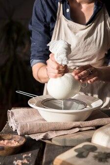 カッテージチーズの準備-チーズクロスを介して牛乳をこする女性。ナッツを浸して皮をむいたアーモンドミルクの準備。ビーガンミルクの代替コンセプト