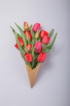 アイスクリームワッフルコニオンコンクリート背景の赤い美しいチューリップ。花の贈り物の概念的なアイデア。春の気分