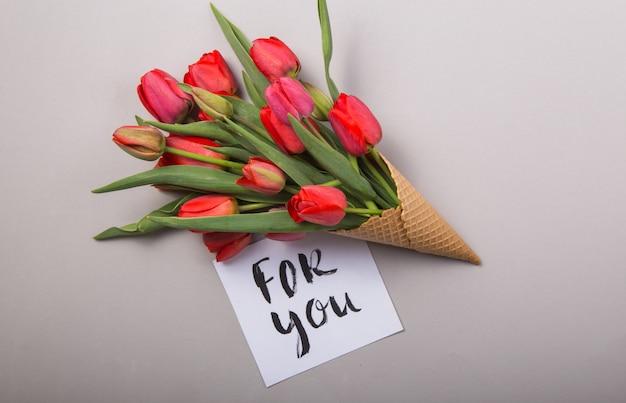 カードとアイスクリームワッフルコーンの赤い美しいチューリップこんにちはコンクリートの背景に。花の贈り物の概念的なアイデア。春の気分