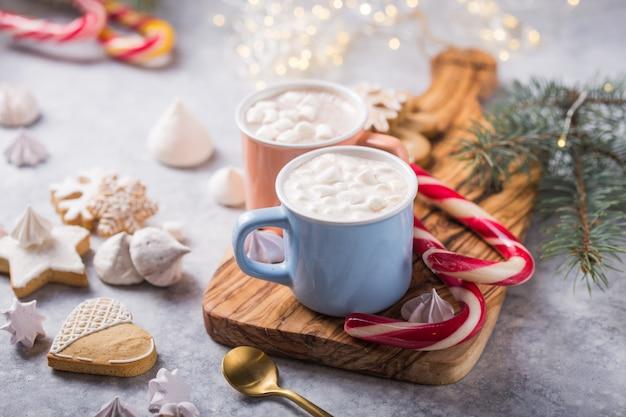 Горячий шоколад какао пьет с зефиром в рождественские кружки цвета на серой поверхности. традиционный горячий напиток, праздничный коктейль на рождество или новый год