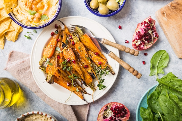Разнообразие здоровых веганских закусок, деликатесные соусы. хумус, жареная морковь, рис с темпе в керамических мисках, вид сверху, еда на растительной основе