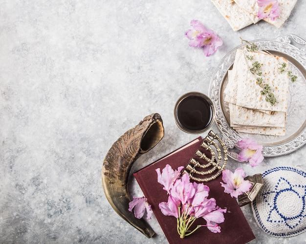 Металлическая пластина с маской кубок киддуш, рога шофар на светлом фоне представлены в виде пасхального седера или праздник с копией пространства. еврейские традиционные предметы, ермолка, талит, молитвенник