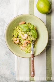 Овощная лапша из кабачков - зеленые кабачки или кабачковые спагетти с креветками на тарелке на сером фоне.