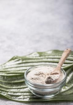 Коллагеновый порошок в стакане. добавки коллагена могут улучшить здоровье кожи, уменьшая морщины и сухость.