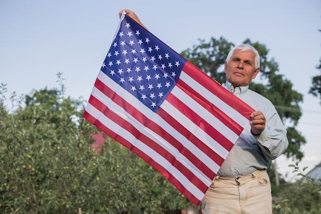 アメリカの国旗を持つ愛国心が強い年配の男性