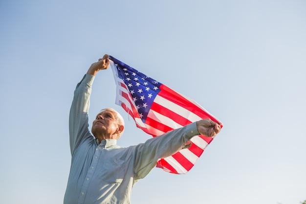 アメリカの国旗を保持している愛国心が強い年配の男性