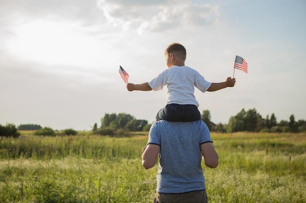 父と少年がアメリカの国旗を保持