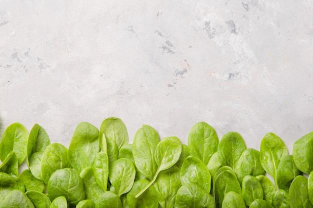 灰色のコンクリートの表面にほうれん草の葉が残っています。きれいな食事、デトックス、ダイエット食品成分