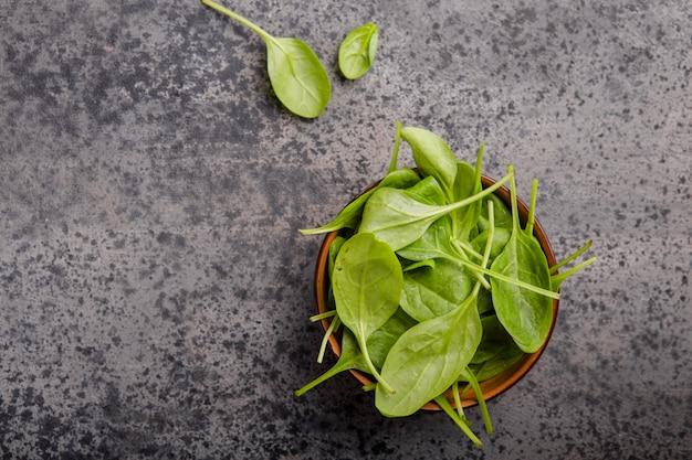 灰色のコンクリート表面にボウルにほうれん草の葉が残ります。きれいな食事、デトックス、ダイエット食品成分