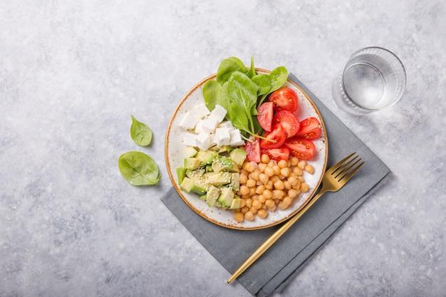Чаша будды с авокадо, нутом, сыром фета, свежим шпинатом, помидорами и стаканом воды.