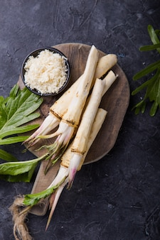 木製のまな板に新鮮なオーガニックホースラディッシュまたはホースラディッシュの根。