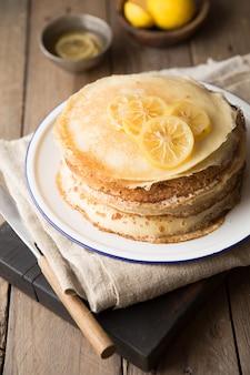 Мед или кленовый сироп наливают на блины. крупным планом вид стека тонких блинов, блины