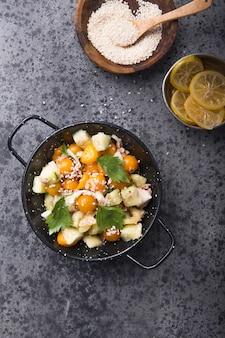 暗い灰色の表面にマグロ、リンゴ、チェリートマト、ゴマを添えたニース風サラダ。フランス料理。 、
