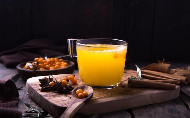 木製テーブルの上のガラスカップでオレンジと海クロウメモドキ茶。ハーブビタミンティー。