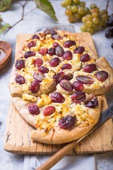 Пицца с козьим сыром и красным виноградом. вегетарианская, без зерна, с низким содержанием углеводов, без глютена концепция диеты